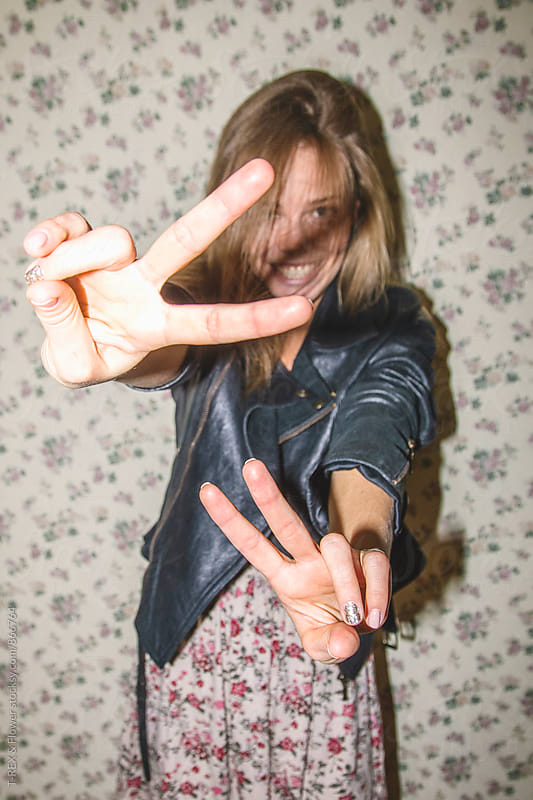 Portrait of smiling young woman showing peace signs to camera by Danil Nevsky for Stocksy United
