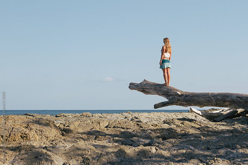 Girl looking out over the ocean on a drift wooden trunk by Melchior van Nigtevecht for Stocksy United
