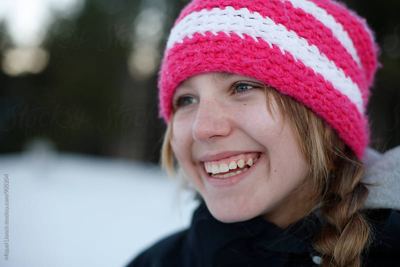 Portrait of a happy young girl in a winter resort by Miquel Llonch for Stocksy United