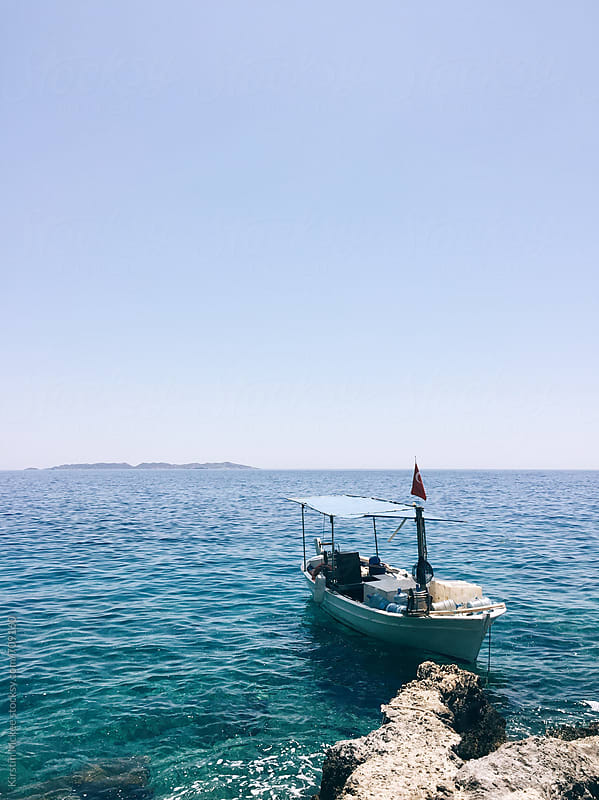 Lone fishing boat in bay, Turkey by Kirstin Mckee for Stocksy United