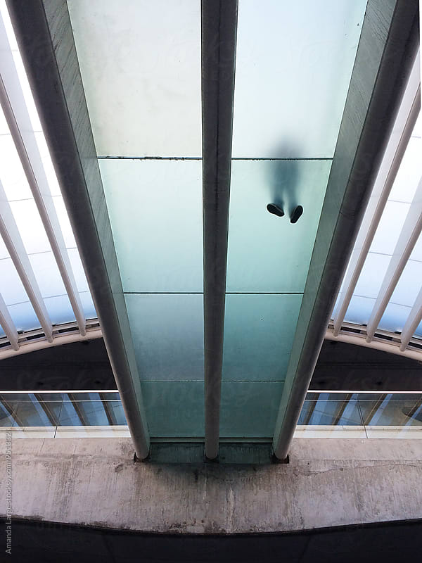 Translucent pedestrian walkway seen from below. by Amanda Large for Stocksy United