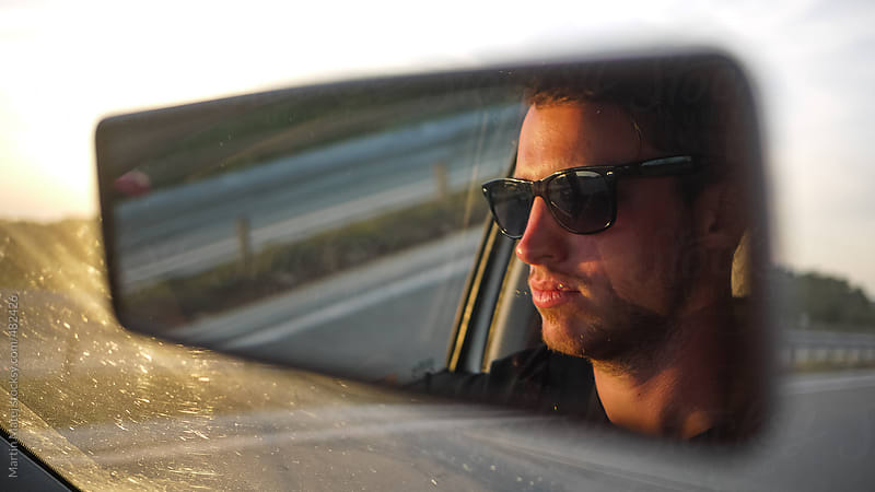 Young driver reflection in the mirror of a car by Martin Matej for Stocksy United