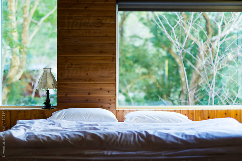 Bedroom with white bed and big window of view in forest by Lawren Lu for Stocksy United