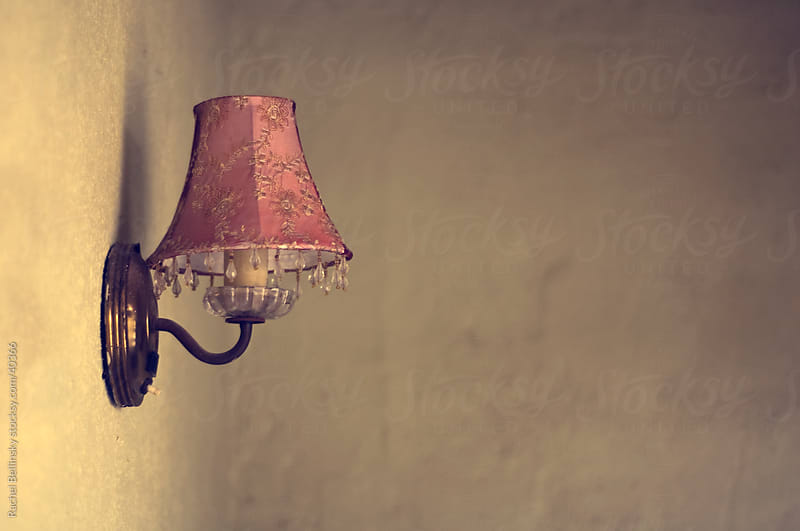 A lone pink vintage lamp on a textured wall by Rachel Bellinsky for Stocksy United
