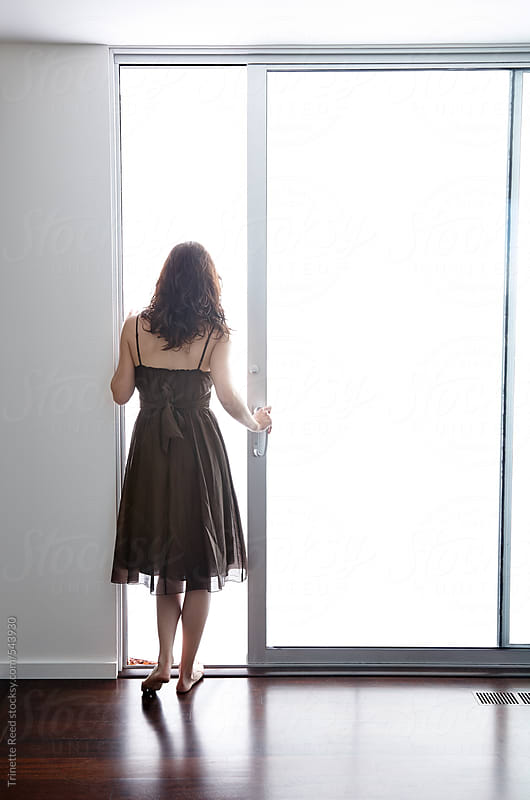 Woman opening sliding glass door at home by Trinette Reed for Stocksy United