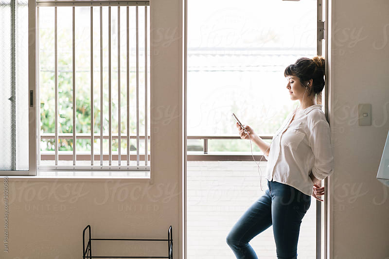 Beautiful young Asian woman using a smartphone by Juri Pozzi for Stocksy United
