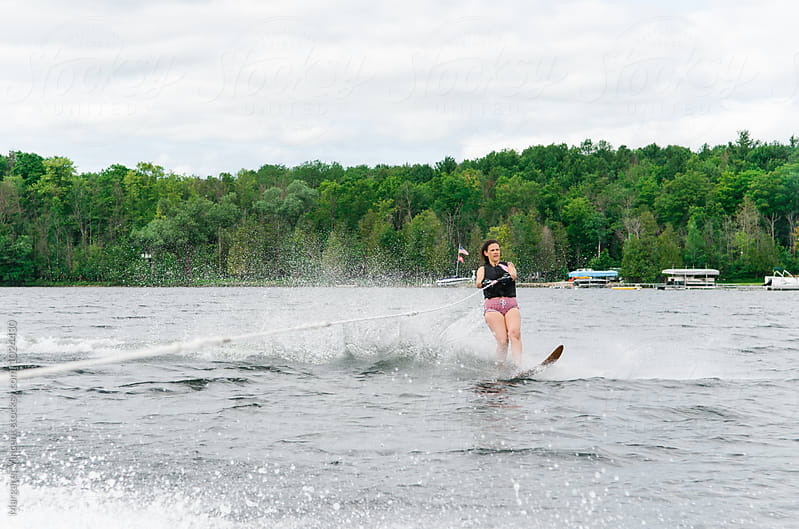 woman water skis outside of wake by Margaret Vincent for Stocksy United