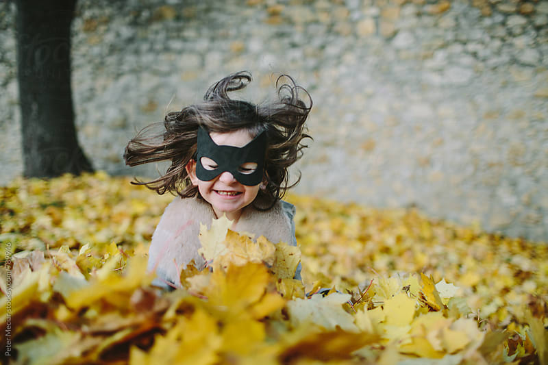 Little girl with a face mask is playing in autumn park  by Peter Meciar for Stocksy United
