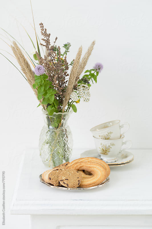 Tea time with cookies and a bouquet of wild flowers picked in the dunes by Elisabeth Coelfen for Stocksy United