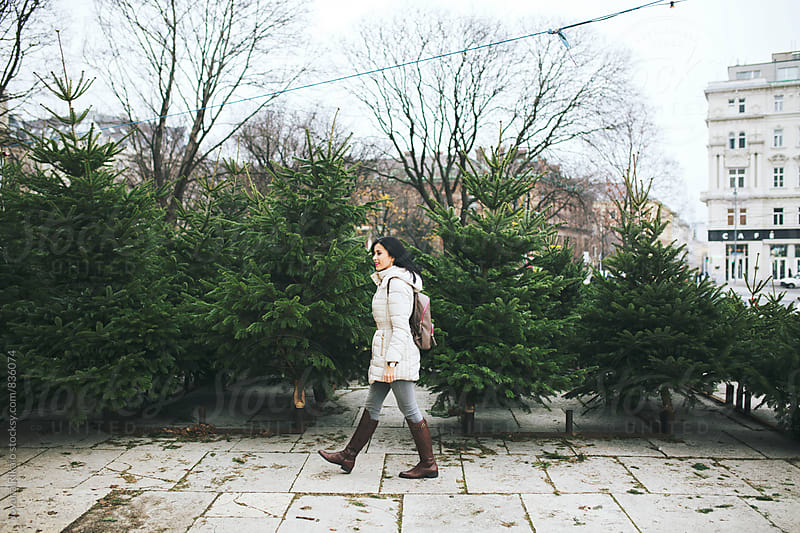 Happy young woman in a Christmas tree store by Jovana Rikalo for Stocksy United