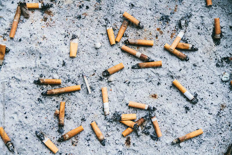 Tobacco cigarettes on sand ashtray by Alejandro Moreno de Carlos for Stocksy United