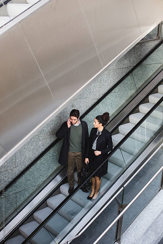Business people on escalators by michela ravasio for Stocksy United
