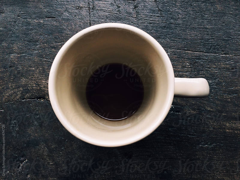 Overhead view of an empty cup of coffee on a wooden table by Greg Schmigel for Stocksy United