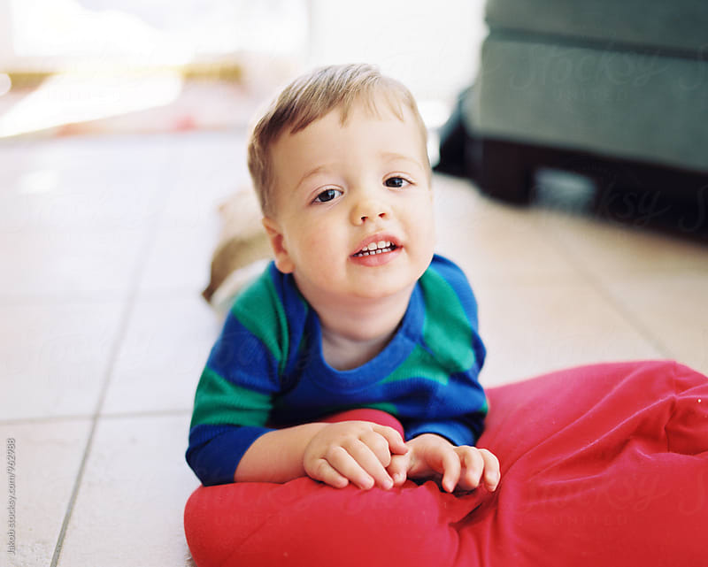 Cute young boy laying on the floor with a red pillow by Jakob for Stocksy United