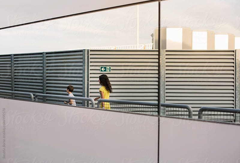 2 kids seen from a mirror  walking by a metal wall  by Beatrix Boros for Stocksy United