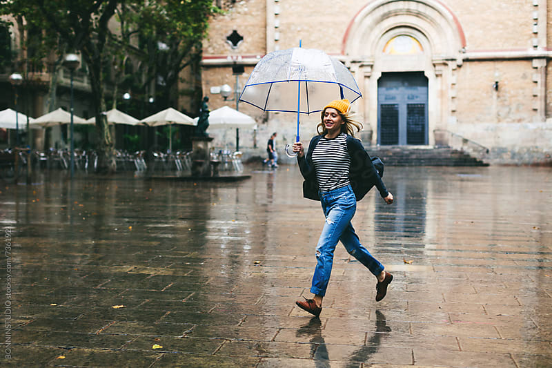 Woman running holding an umbrella on a rainy day. by BONNINSTUDIO for Stocksy United
