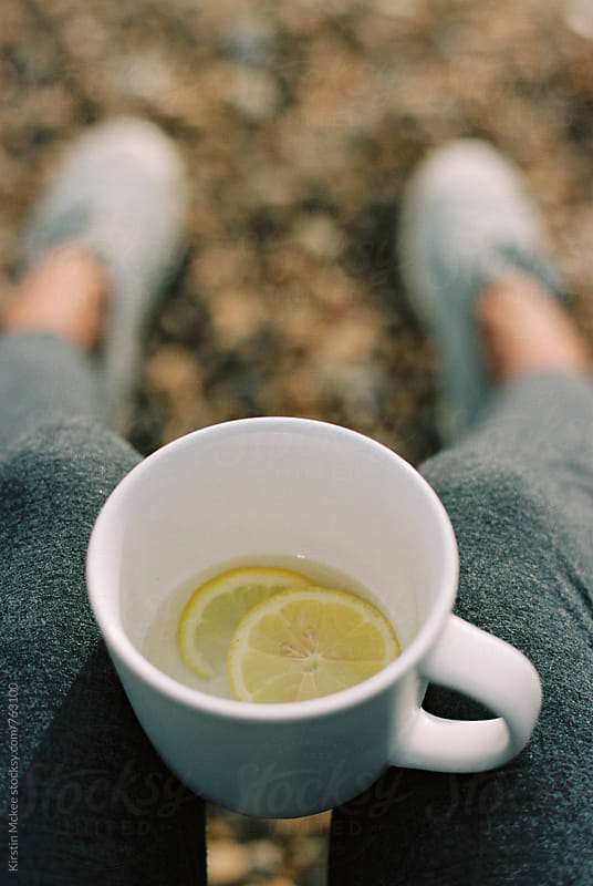 Sitting on the beach with a cup of lemon tea by Kirstin Mckee for Stocksy United