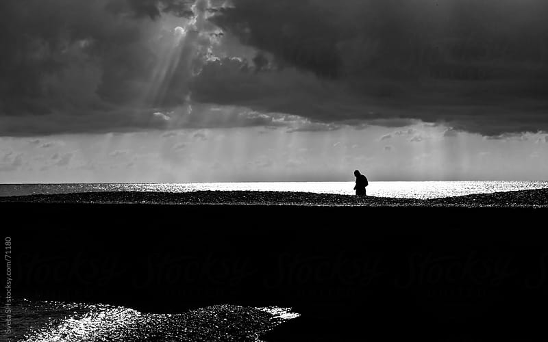 Silhouette of a man walking to the sea on a background of water and sunlight by Sveta SH for Stocksy United