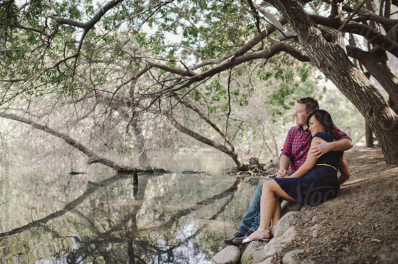 Romantic couple cuddling by lake in nature by Kristin Rogers Photography for Stocksy United