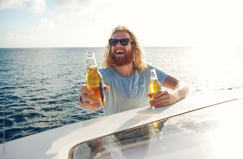 Bearded man on a boat handing out beers on a sunny day by Denni Van Huis for Stocksy United