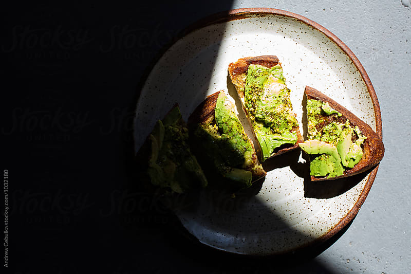 Avocado toast on white ceramic plate by Andrew Cebulka for Stocksy United