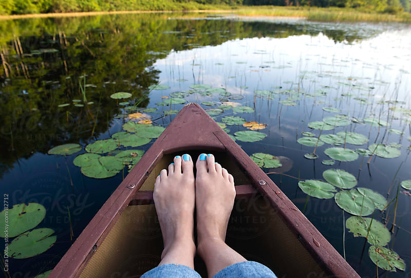 Woman's feet rest on the front of a canoe floating through lily pads on a river by Cara Dolan for Stocksy United