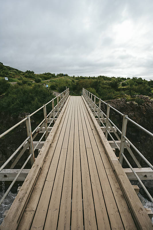 Wooden bridge over a small river by Gabriel Tichy for Stocksy United