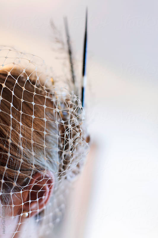 The side view of a woman's head wearing a bridal headpiece made of netting and porcupine quills. by Holly Clark for Stocksy United