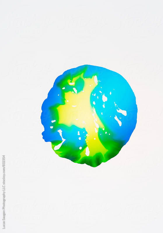Blue and green puddles seem to form a small world. by Lucas Saugen for Stocksy United