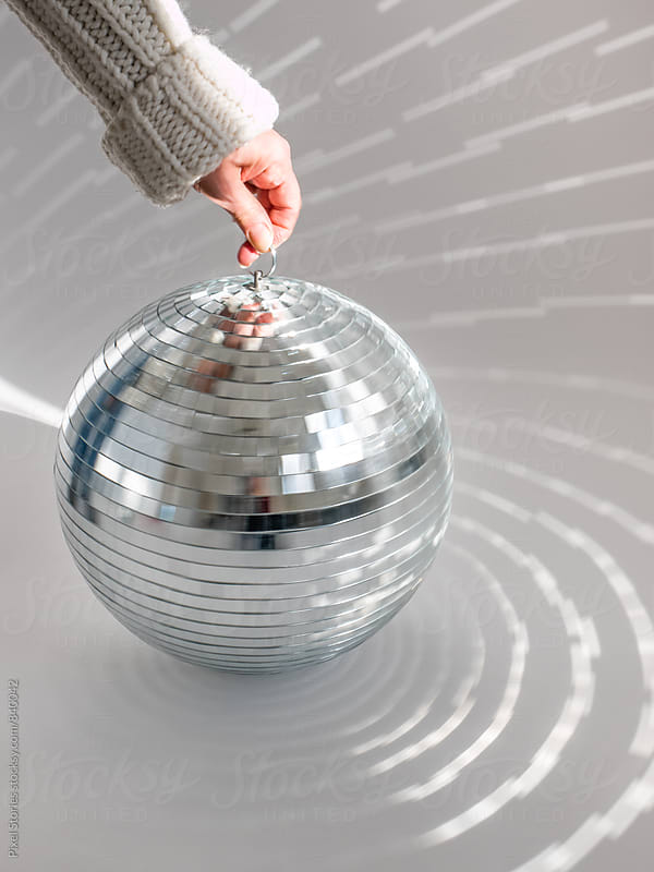 Hand spinning disco ball by Pixel Stories for Stocksy United