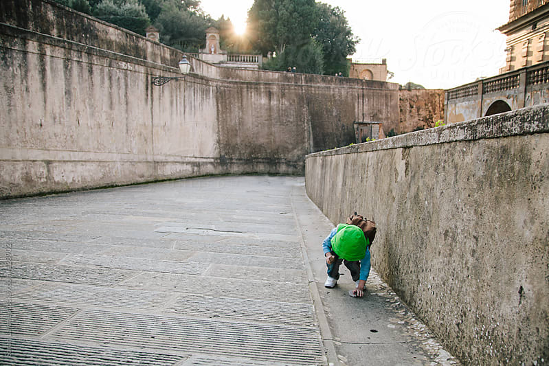 a little boy picking up a pebble off the street in florence by Sarah Lalone for Stocksy United
