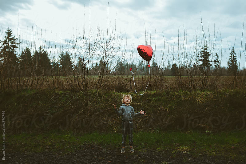 Child Jumping Throwing Balloon  by Bryan Rupp for Stocksy United