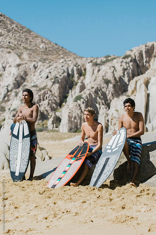 A group of friends hanging out on a beach waiting to hit the surf by Ania Boniecka for Stocksy United