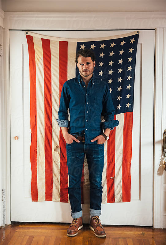 Hipster man standing in front of American Flag by Trinette Reed for Stocksy United