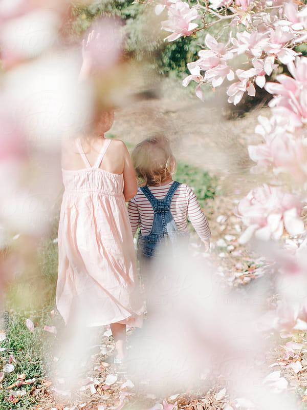 two little girls playing beneath spring trees by Meaghan Curry for Stocksy United
