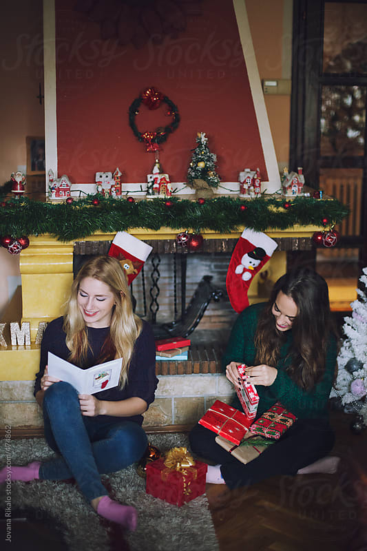 Two female friends opening Christmas presents by Jovana Rikalo for Stocksy United