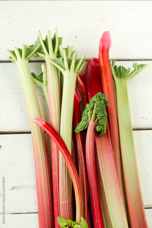 Rhubarb stalks on white wooden board by Noemi Hauser for Stocksy United