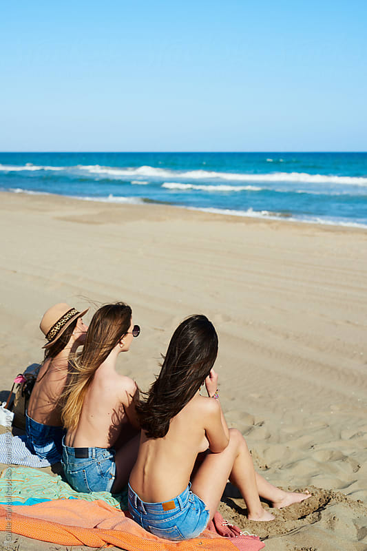 Back view of topless girls getting tanned on beach blanket by Guille Faingold for Stocksy United