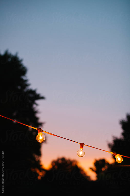 string lights against a sunset sky by Sarah Lalone for Stocksy United