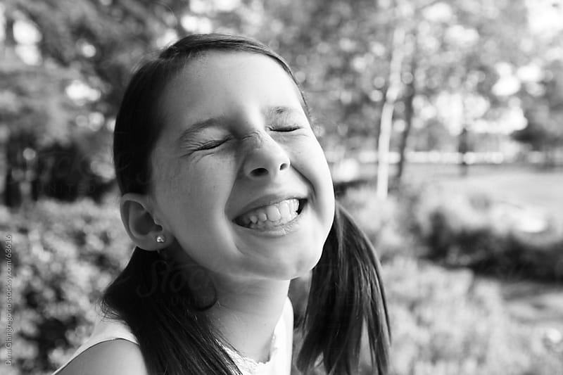 Girl smiling with scrunched up nose and eyes closed by Dina Giangregorio for Stocksy United