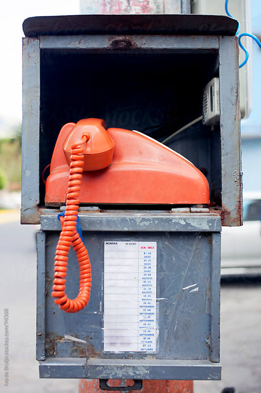 An old school telephone in a box on the street by Ivo de Bruijn for Stocksy United