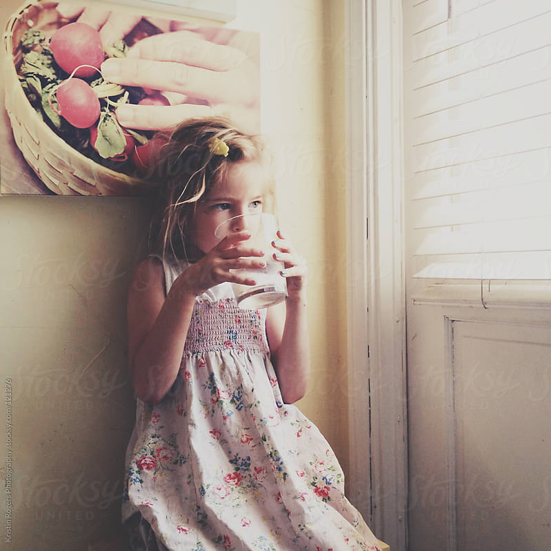 young girl drinking by window in kitchen by Kristin Rogers Photography for Stocksy United
