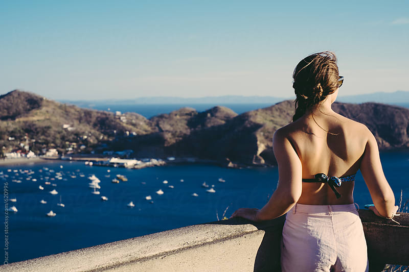 Woman overlooking the bay by Oscar Lopez for Stocksy United