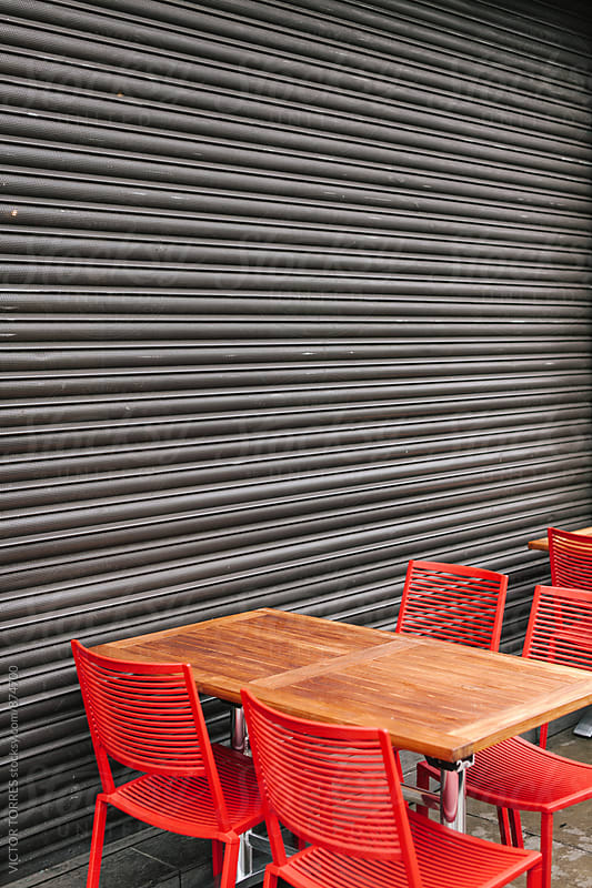 Outdoor Restaurant Table Besides a Closed Metallic Door by VICTOR TORRES for Stocksy United