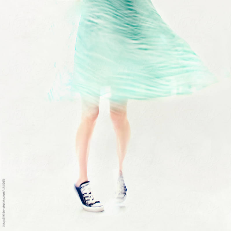 Twirly girl in blue canvas sneakers by Jacqui Miller for Stocksy United