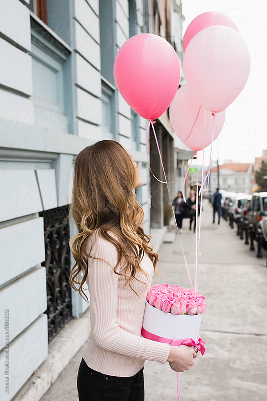 Young woman holding colorful pink balloons and box full of pink roses by Jovana Rikalo for Stocksy United