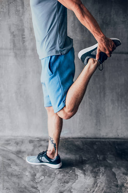 Man Stretching His Leg After a Workout by Lumina for Stocksy United