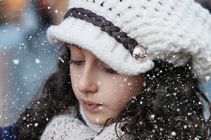 Headshot of a preteenager girl who is looking away in the Winter with snowflakes by Beatrix Boros for Stocksy United