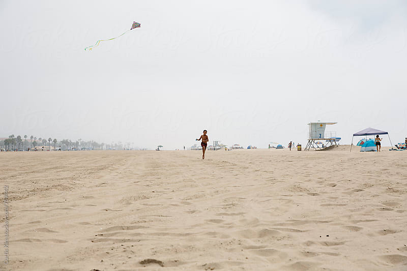Boy running and flying a kite on the beach by Curtis Kim for Stocksy United