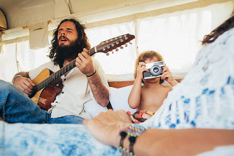On The Road - Bearded Male Hippie Singing With Child and Wife in Camper Van by VISUALSPECTRUM for Stocksy United